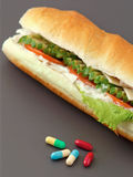 Pills and two hot dogs with various ingredients. Royalty Free Stock Image