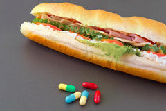 Pills and two hot dogs with various ingredients. Stock Photos