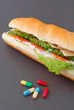 Pills and two hot dogs with various ingredients. On grey background Stock Photography