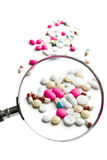 Pills under magnifying glass Royalty Free Stock Photos