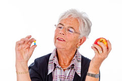 Pills or vitamin. The picture shows a Portrait of Senior Woman with apple in one hand and pill in the other Royalty Free Stock Images