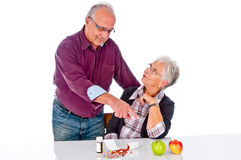 Pills or vitamin. The picture shows  Senior couple thinking about taking fruit and pills Stock Photos