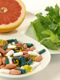 Pills vs vitamins, closeup, isolated. Choice between natural vitamins and supplements Stock Images