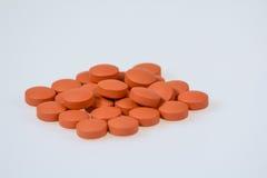 pills on white background. Brown Orange medicine pills piled and  on white Stock Photos