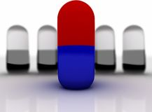 Pills on a white background. One red-blue capsule in a pile of black-white. Pills on a white background Royalty Free Stock Photo