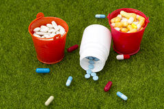 Pills,white bottle of pills and two buckets filled with colorful tablets Stock Photo