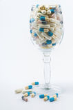 Pills in wine glass. Isolated white background Royalty Free Stock Images