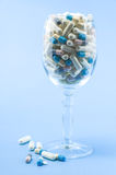 Pills in wine glass. On light blue background Royalty Free Stock Image
