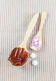 Pills in wooden spoon on brown cloth Royalty Free Stock Photography