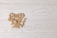 Pills on wooden table. Brown pills on wooden table Royalty Free Stock Image