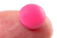 Pillule rose sur le doigt Photographie stock libre de droits