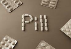 Pillules blanches formant le mot - pilule près de sont les comprimés au-dessus du fond gris image stock