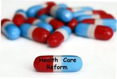 Pillules de réforme de soins de santé d'isolement sur le blanc Photo libre de droits