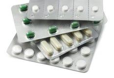 Pillules emballées divers par clinquant sur le blanc Image stock