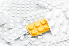 Pillules en module jaune au-dessus des tablettes blanches Photos libres de droits