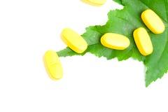 Pillules jaunes de vitamine au-dessus de lame verte Photo stock
