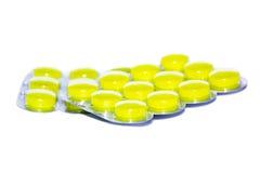 Pillules jaunes sur le fond blanc Photographie stock