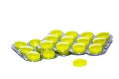 Pillules jaunes sur le fond blanc Images libres de droits