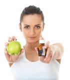 Pillules ou pomme, deux sources des vitamines, d'isolement Photographie stock