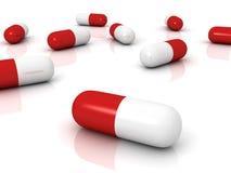 Pillules pharmaceutiques rouges de capsules sur la surface blanche Photographie stock libre de droits