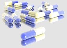 pillules r3fléchissantes bleu-blanches sur le support en verre Photographie stock