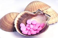 Pillules roses étendues dans un interpréteur de commandes interactif de mer Image stock