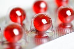 Pillules rouges dans l'ampoule Macro closeup sur un backgr blanc Photographie stock