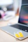 Pillules sur un ordinateur portatif Image libre de droits