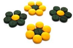 Pillules vertes et jaunes sous forme de fleurs Photographie stock libre de droits