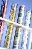 Pillules, vitamines et argent dans des tubes à essai Photographie stock
