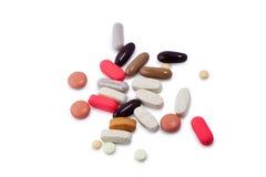 Pillules, vitamines et suppléments assortis sur le blanc Photographie stock libre de droits