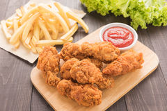 Pilon de poulet frit et pommes frites sur la table en bois Images libres de droits
