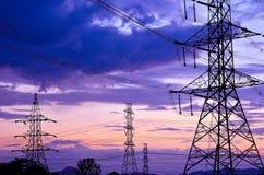 Pilone ad alta tensione di elettricità contro cielo blu Fotografia Stock
