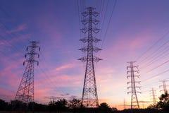 Pilone ad alta tensione di elettricità della siluetta sul fondo di alba Immagini Stock