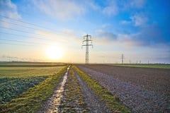 Pilone con le linee ad alta tensione nel paesaggio rurale Immagini Stock