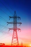 Pilone della siluetta, torre di elettrico ad alta tensione Fotografia Stock