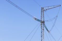 Pilone della trasmissione di elettricità profilato su cielo blu Fotografie Stock Libere da Diritti