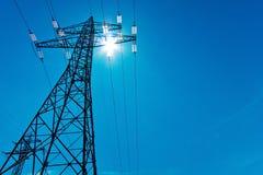 Pilone di elettricità con il sole ed il cielo Fotografia Stock