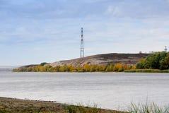 Pilone di elettricità e della linea ad alta tensione sulla linea costiera del fiume Fotografie Stock Libere da Diritti