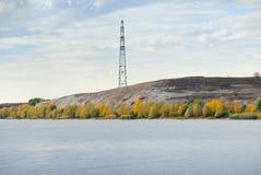 Pilone di elettricità e della linea ad alta tensione sulla linea costiera del fiume Immagini Stock Libere da Diritti