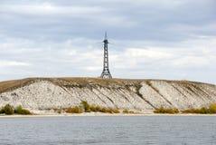 Pilone di elettricità e della linea ad alta tensione sulla linea costiera del fiume Fotografia Stock