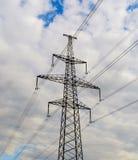 Pilone di elettricità profilato sul fondo del sole del cielo blu Torretta ad alta tensione Fotografia Stock Libera da Diritti