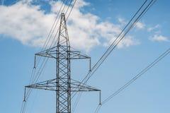Pilone e cavi elettrici della torre su un cielo blu con le nuvole Immagine Stock
