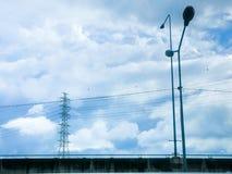 Pilone e linea elettrica di alta tensione in cielo nuvoloso Immagine Stock