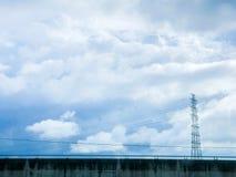 Pilone e linea elettrica di alta tensione in cielo nuvoloso Immagini Stock Libere da Diritti