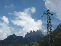 Pilone e montagne di elettricità Fotografie Stock