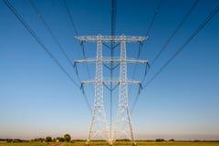 Pilones de alto voltaje contra un cielo azul foto de archivo