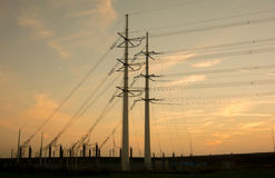 Pilones de la electricidad con el fondo anaranjado imágenes de archivo libres de regalías