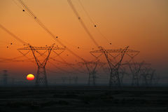 Pilones de la electricidad con el sol de configuración Imagenes de archivo