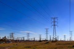 Pilones de la electricidad contra el cielo azul en el terreno desigual foto de archivo libre de regalías